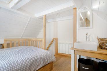 Slaapkamer van vakantiehuis Murol met tweepersoonsbed wastafel en toilet