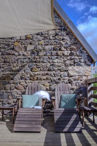 Twee comfortabele zonnestoelen op het grote prive terras van het vakantiehuis Murol in Auvergne-Rhône-Alpes, Frankrijk